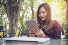 A smiley beautiful Asian woman holding ,using and looking at tablet pc with laptop on glass table sitting at outdoor Stock Image