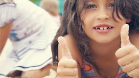 Closeup image of smiling little girl with hands in sand showing thumbs up. royalty free stock images
