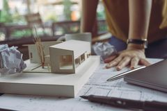 Closeup image of a stressed architects thinking and drawing shop drawing paper with architecture model and laptop on table. While fail stock images