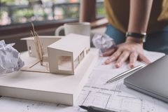 Closeup image of a stressed architects thinking and drawing shop drawing paper with architecture model and laptop on table. While fail stock photography