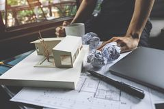 Closeup image of a stressed architects thinking and drawing shop drawing paper with architecture model and laptop on table. With feeling fail stock photography