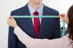 Closeup image of tailor taking measurements for business jacket suit. Businessman in red tie and blue suit at studio isolated royalty free stock photos
