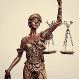 Closeup image of Themis goddess or lady justice holding scale blindfold on light background stock image