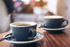 Closeup image of two blue cups of hot latte coffee and Americano coffee on vintage wooden table. In cafe royalty free stock photography