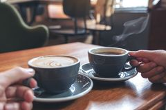 Two people`s hands holding coffee and hot chocolate cups on wooden table in cafe royalty free stock photos
