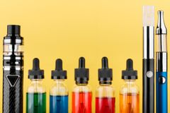 Vaping devices and unfocused bottles with vape liquid on yellow background. Closeup image of vaping device collection and bottles with colored vape liquid on royalty free stock photography