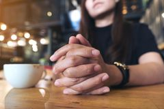 Closeup image of a woman clap one`s  hand , sitting and thinking in cafe with a white cup of coffee. On wooden table Royalty Free Stock Photography