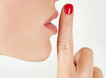 Closeup image of a woman gesturing quiet from side view isolated. On white Royalty Free Stock Photo