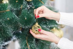 Closeup image of woman holding golden Christmas bauble Royalty Free Stock Image