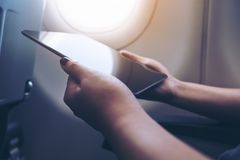 Closeup image of a woman holding and looking at black tablet pc next to an airplane window with clouds and sky Royalty Free Stock Photos