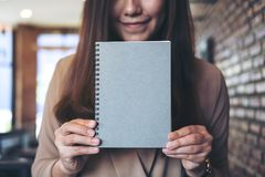 A woman holding and showing blank grey notebook in office. Closeup image of a woman holding and showing blank grey notebook in office Stock Images