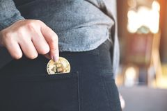A woman picking up and dropping bitcoin into a black jean pocket. Closeup image of a woman picking up and dropping bitcoin into a black jean pocket Royalty Free Stock Photography
