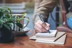 A woman`s hand writing on blank notebook stock photos
