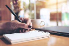 Closeup image of woman`s hand writing on a blank notebook with laptop , tablet and coffee cup on wooden table. Background royalty free stock photography