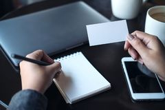 A woman`s hands holding empty white business card and writing on notebook. Closeup image of a woman`s hands holding empty white business card and writing on Royalty Free Stock Photography