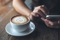 A woman`s hands holding , using and pointing at smart phone with latte coffee cup on wooden table in vintage cafe Stock Photography