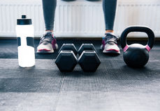 Closeup image of a woman sitting at gym. With dumbbells, shaker and weight Stock Photo