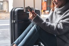 A woman sitting and using mobile phone with a black baggage for traveling royalty free stock image