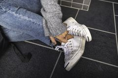 A woman wearing jean and white sneakers touching her leg while sitting on the floor. Closeup image of a woman wearing jean and white sneakers touching her leg royalty free stock photos
