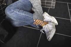 A woman wearing jean and white sneakers touching her leg while sitting on the floor. Closeup image of a woman wearing jean and white sneakers touching her leg stock photos