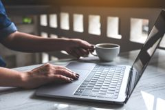 A woman working and typing on laptop keyboard while drinking coffee in office royalty free stock photo