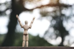 Wooden figure model of a man rising hands and standing on wooden table with blur background. Closeup image of wooden figure model of a man rising hands and stock photo