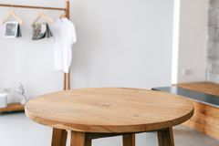 A wooden table and clothes rank in minimalist house. Closeup image of a wooden table and clothes rank in minimalist house stock photos