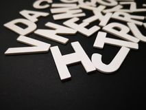 Closeup image of wooden white alphabet letters with black color background. royalty free stock photo