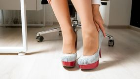 Closeup photo of young elegant woman taking off high heels shoes. Closeup image of young elegant woman taking off high heels shoes stock photos
