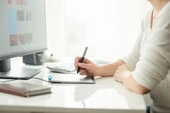 Closeup image of young female graphic designer holding stylus and working with graphic tablet royalty free stock image