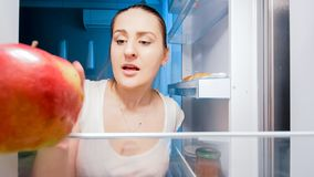 Closeup image of young hungry woman looking for something to eat in refrigerator at night. Closeup photo of young hungry woman looking for something to eat in stock images