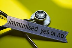 Closeup immunised yes or no with stethoscope concept inspiration on yellow background stock photography