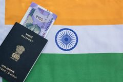 Closeup of Indian passport with Indian currency on Indian flag as a background stock photo