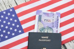 Closeup of Indian passport with currency on USA or america`s flag as a background stock photo