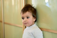 Closeup indoor portrait of a baby boy with naughty hair. The various emotions of a child. royalty free stock image
