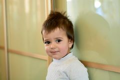 Closeup indoor portrait of a baby boy with naughty hair. The various emotions of a child. stock photos