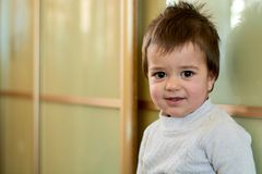Closeup indoor portrait of a baby boy with naughty hair. The various emotions of a child. stock photo