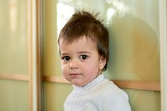 Closeup indoor portrait of a baby boy with naughty hair. The various emotions of a child. royalty free stock photography