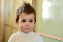 Closeup indoor portrait of a baby boy with naughty hair. The various emotions of a child. stock photography