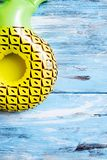 Inflatable pineapple on a blue rustic wooden surface. Closeup of an inflatable pineapple on a blue rustic wooden surface with some blank space stock image