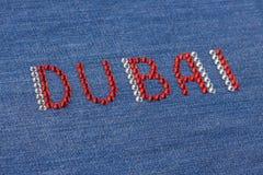Closeup inscription Dubai, inlaid rhinestones on denim. Stock Photography