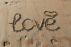 Closeup of Inscription of `Love`, a symbol of heart and footprints in the sand. royalty free stock photos