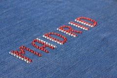 Closeup inscription Madrid, inlaid rhinestones on denim. Stock Photos