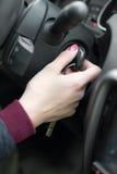 Closeup inside vehicle of hand holding key in ignition, start engine key Stock Photography
