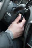 Closeup inside vehicle of hand holding key in ignition, start engine key Royalty Free Stock Photos