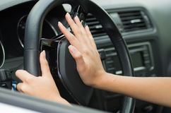 Closeup inside vehicle of hand pushing on steering wheel honking horn, black interior background, female driver concept.  Stock Photography