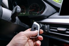Closeup inside vehicle of man hand holding wireless key ignition. Start engine key. Hand holding car key remote. Modern car backgr. Ound. Interior details. Car stock photography