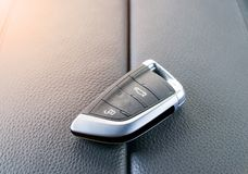 Closeup inside vehicle of wireless key ignition. Start engine key. Car key remote in black perforated leather interior. Car backgr royalty free stock photo