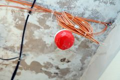 Closeup installation and repair of electric cable, smoke detector, fire alarm system before installing stretch or suspended. Closeup installation and repair of royalty free stock images