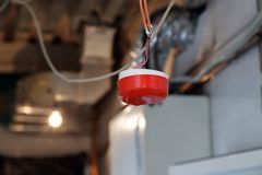 Closeup installation and repair of electric cable, smoke detector, fire alarm system before installing stretch or suspended. Closeup installation and repair of stock photo